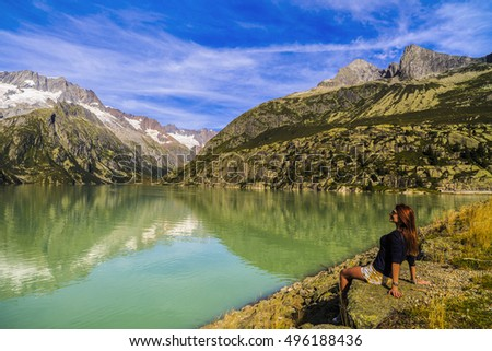 Women admire a beautiful mountain landscape with lake