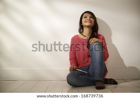 Women and health, relaxed Asian girl looking at pregnancy test kit sitting on floor at home - stock photo