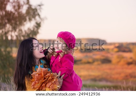 women and little girl walking in autumnal field - stock photo