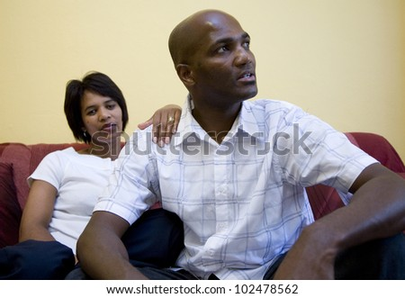 Women and man on couch with man looking away
