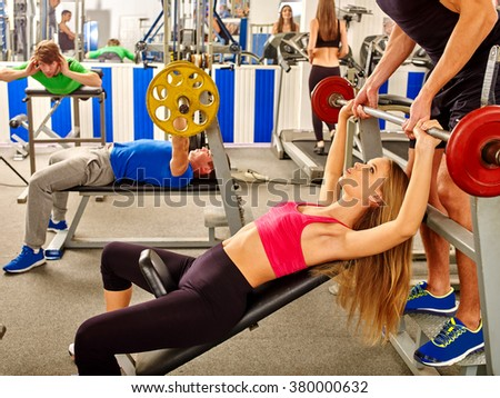 Women and men lifting barbell at gym and  insures coach. - stock photo