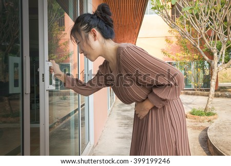 Women and stomachache shocking pain with home office background and copy space - stock photo