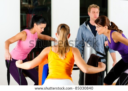 women and trainer in gym in front of a exercising machine doing fitness exercises - stock photo