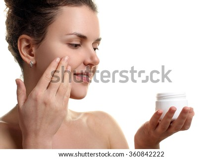 Women apply moisturizer on your face on a white isolated background - stock photo