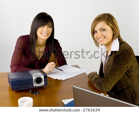 Women are sitting at conference's table and looking at the camera with smile. There's multimedia projector and laptop on the table. - stock photo