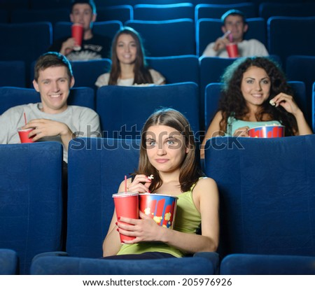 Women at the cinema. Beautiful young women eating popcorn while watching movie at the cinema