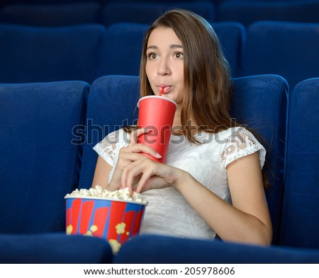 Women at the cinema. Beautiful young women eating popcorn while watching movie at the cinema - stock photo