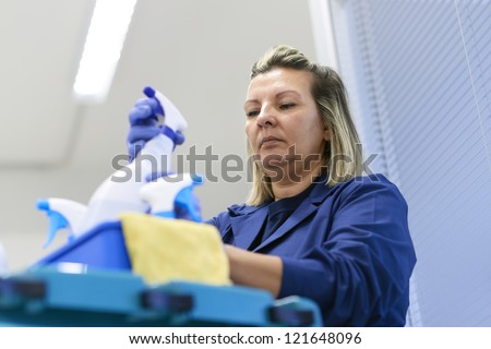 Women at work, portrait of professional female cleaner arranging bottles of detergents on trolley in office - stock photo