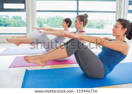 Women at yoga class in boat pose in fitness studio - stock photo