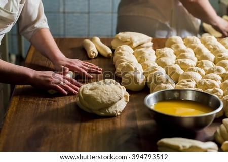Women bake pies. Confectioners make desserts. Making buns. Dough on the table. Knead the dough. - stock photo