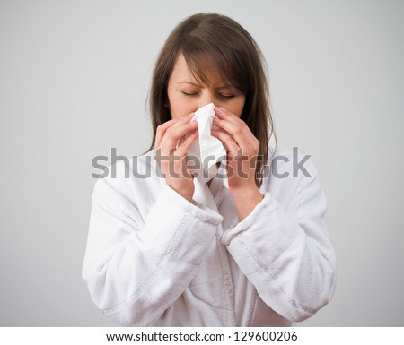 Women blows nose in bathrobe on grey background. See more