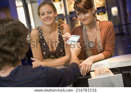 Women buying movie tickets at the box office.
