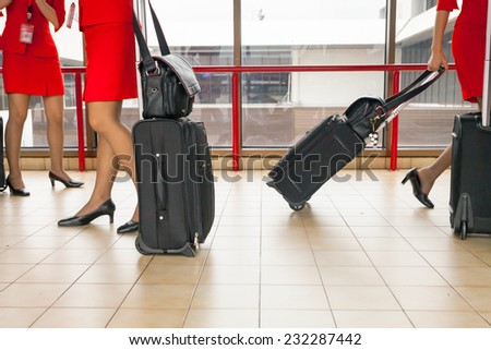 Women carries their luggage at the airport terminal - stock photo