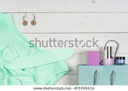 Women clothing set and accessories on a rustic wooden background.Top view