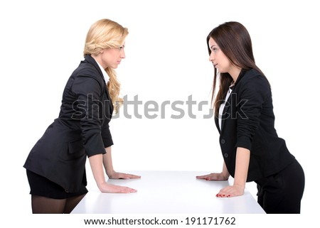 Women confrontation. Two angry women looking at each other while holding their hands on the table - stock photo