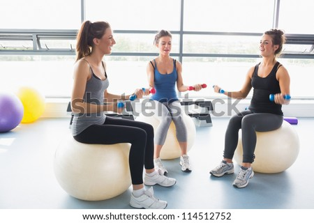 Women doing work out on exercise balls in a gym - stock photo