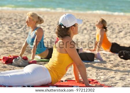 Women doing yoga exercise on an empty beach - stock photo
