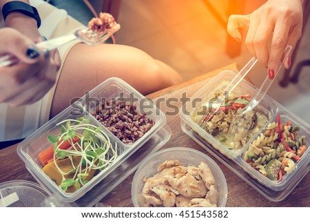 Women eating Healthy food in lunch box on wooden table.  Healthy food concept