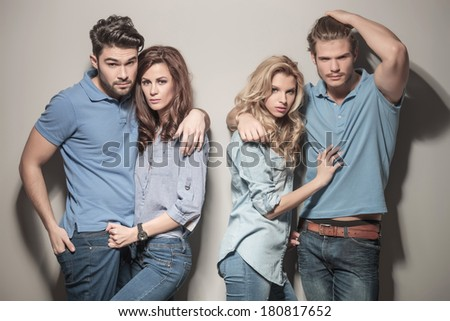 women embracing their boyfriends while posing in studio, dressed in casual jeans clothes - stock photo