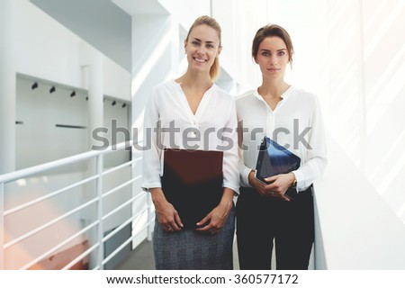 Women employees resting in office interior after entering information from paper documents in touch pad, two female partners holding digital tablet and folder after preparing for meeting with clients - stock photo