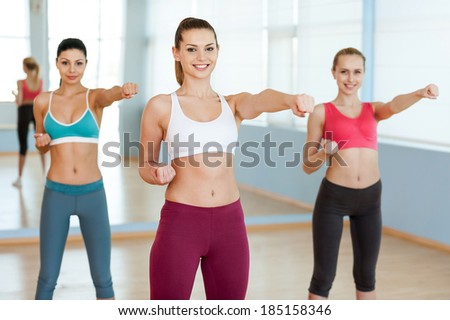 Women exercising. Three beautiful young women in sports clothing exercising and looking at camera - stock photo