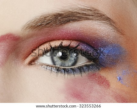 women face close up with blue pink orange purple eye - stock photo