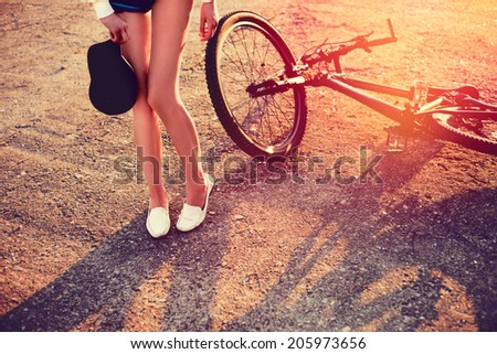 Women feet alongside a bicycle. Colorful outdoor portrait of young pretty fashion model with bike. summer sun-rays