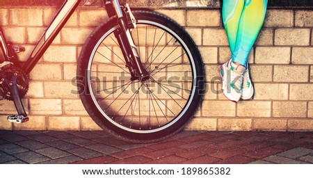 Women feet in sneakers alongside a bicycle