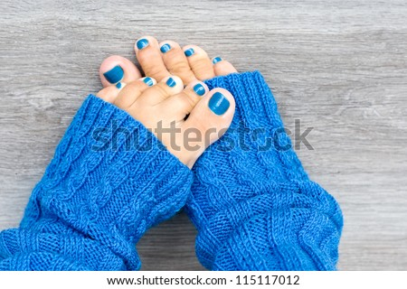 Women feet with blue nails manicure in blue socks - stock photo