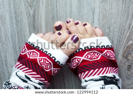Women feet with pedicure in a christmas socks - stock photo