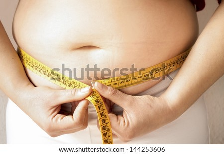 women female checking fats on her body with a meter - stock photo