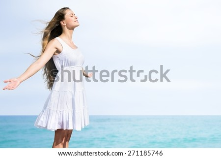 Women. Free woman enjoying freedom feeling happy at beach at sunset. Beautiful serene relaxing woman in pure happiness and elated enjoyment with arms raised outstretched up. Asian Caucasian female - stock photo