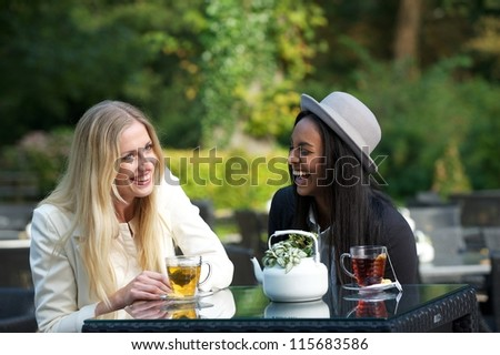 Women friends laughing and enjoying their tea outdoors - stock photo