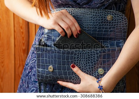 Women get out fashion thing from blue fashionable handbag. - stock photo