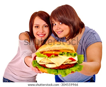 Women giving hamburger in camera . Fast food in our lives - stock photo