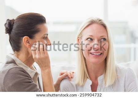 Women gossiping at home in living room - stock photo