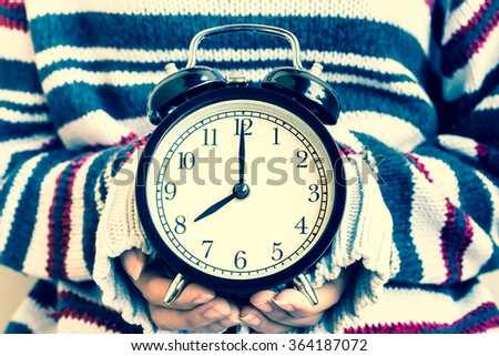 Women hand hold a vintage alarm clock in vintage tone
