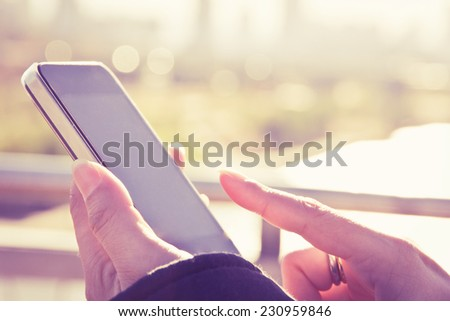 Women hand holding a smart phone with sunrise background - stock photo