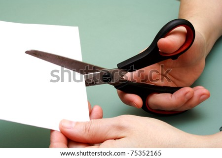 women hand is cutting paper with scissors - stock photo