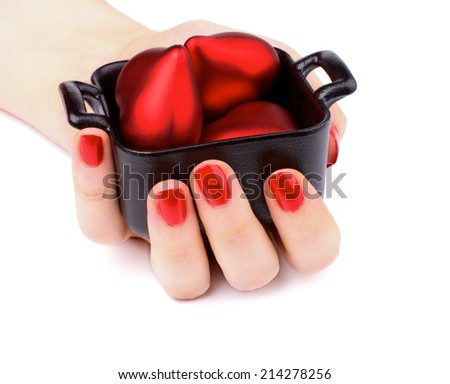 Women Hand with Red Manicure Hold Black Container with Red Plastic Hearts isolated on white background - stock photo