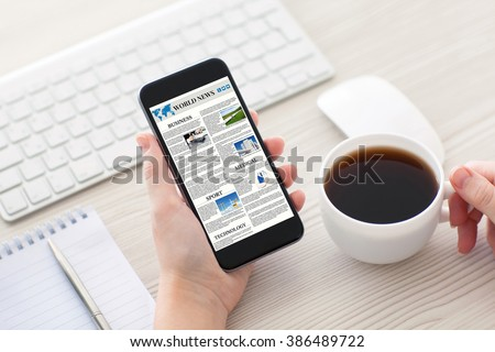 Women hands holding phone with world news site on the screen and cup of coffee in the office - stock photo