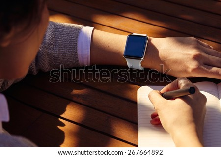 Women hands with smart watch working on table - stock photo