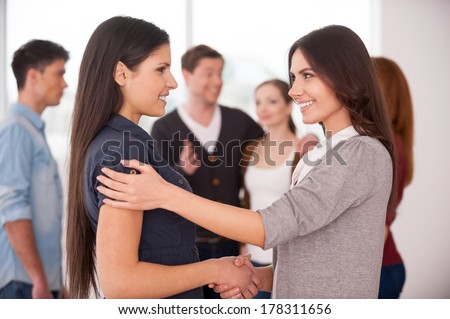 Women handshaking. Two cheerful young women handshaking while group of people communicating on background - stock photo