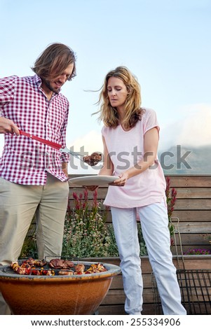 Women helping at the outdoor rooftop barbeque with a plate while man serves healthy chicken kebab - stock photo
