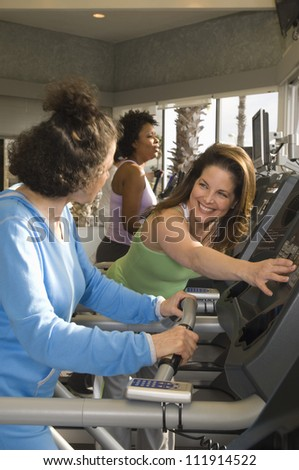 Women helping each other riding an exercise bike - stock photo