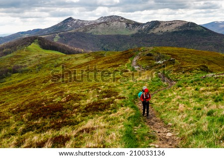 Women hiker is ascending the steep slope with the heavy backpack as the part of the expedition in Bieszczady national park, Poland - stock photo