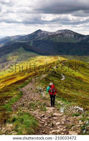 Women hiker with heavy backpack is climbing the ridge of Bieszczady mountains during her wild expedition through Poland and Slovakia - stock photo
