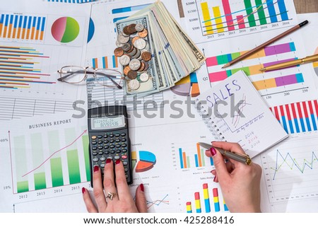 women hold calculator above business chart with money - stock photo