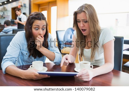 Women holding a tablet and looking surprised while sitting in canteen - stock photo