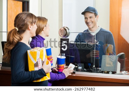 Women holding snacks while buying movie tickets from male seller at box office - stock photo